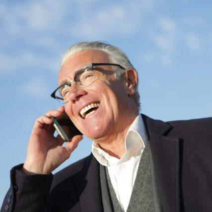 cheerful-senior-businessman-talking-on-smartphone-on-street-3783546